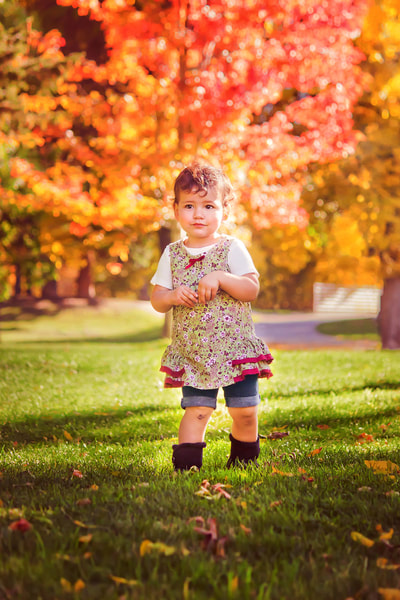 Little girl with brown curly hair in the open park with gorgeous fall trees behind after retouching.