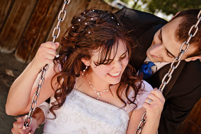 Excited newly wed couple on a swing, after retouch.